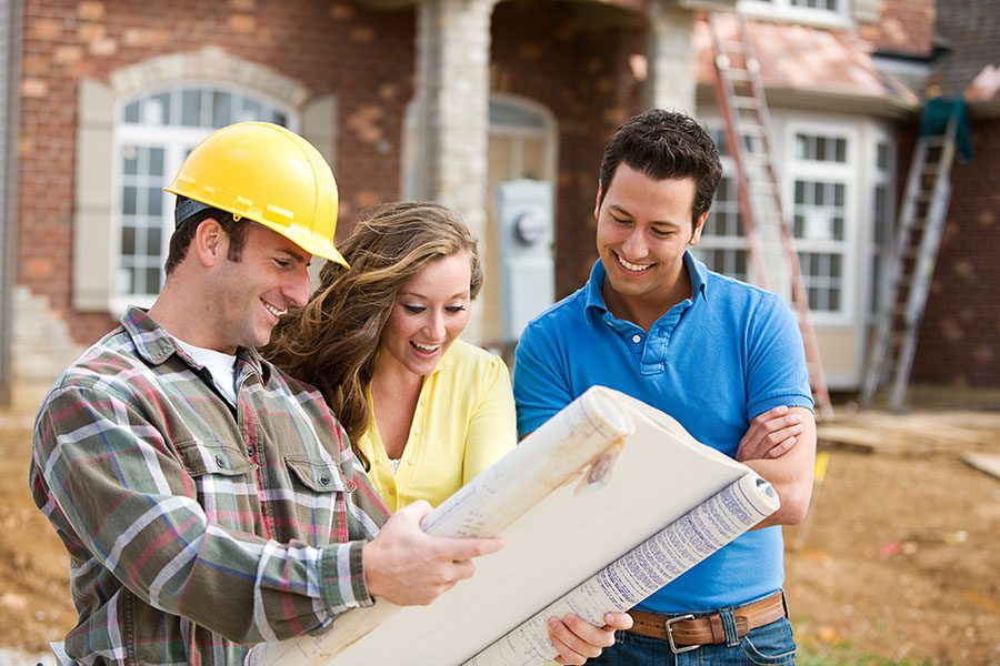 Specialized Business Insurance - Construction Worker Showing New House Plans To A Smiling Couple