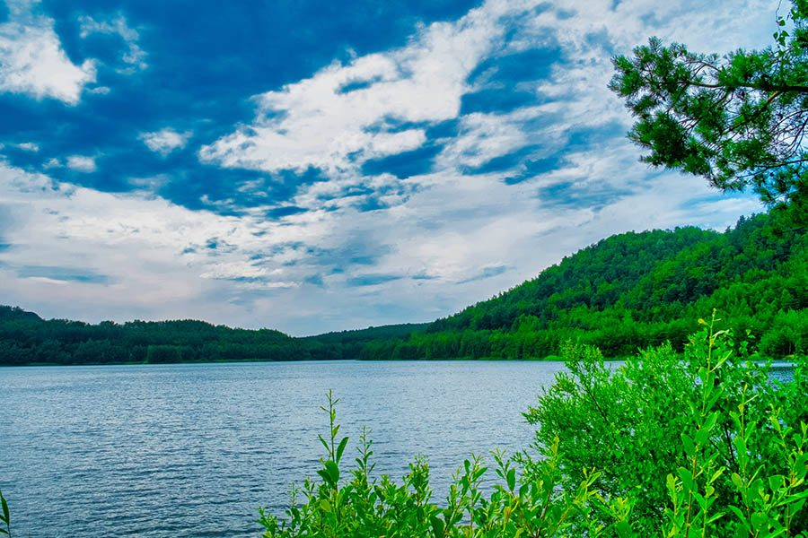 Sterling, MA Insurance - Wachusett Reservoir with Green Mountains and a Cloudy Blue Sky