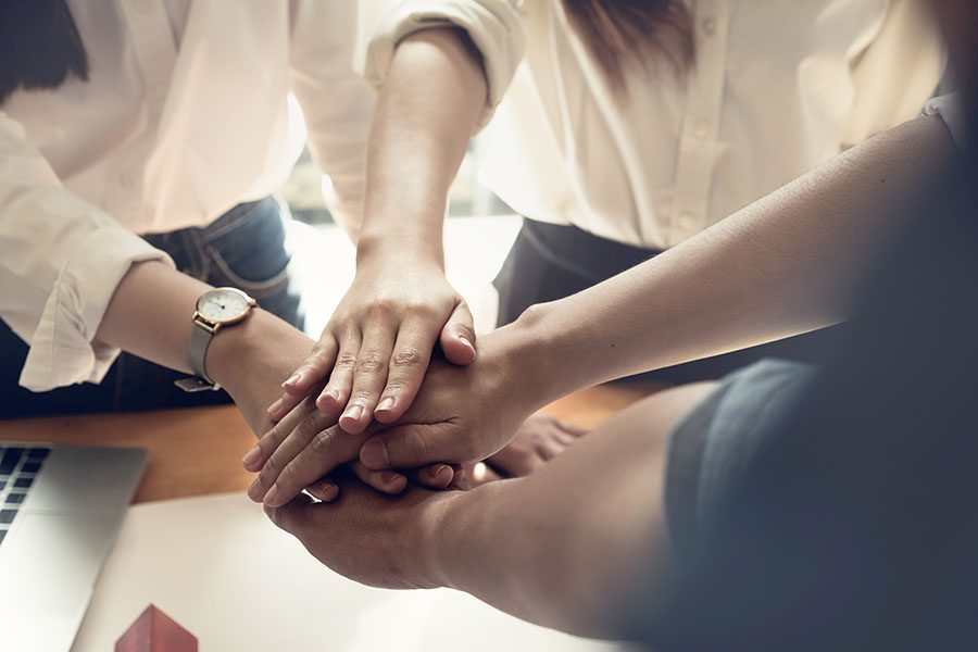 About Our Agency - Group Of Coworkers At Office Joining Hands Together In Unity