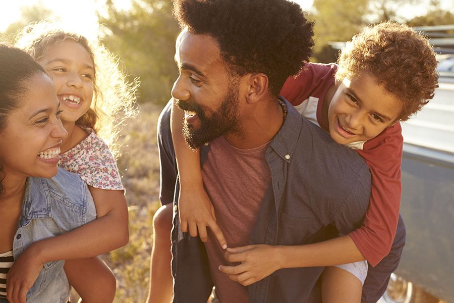 Personal Insurance - Smiling Mother And Father On Road Trip Giving Piggyback Rides To Their Kids