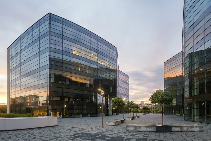 Business Insurance - Modern Office Building in the Evening with Landscaped Trees and City in the Background
