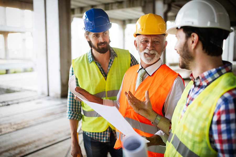 Specialized Business Insurance - Happy Construction Workers Looking Over Plans at a Construction Site