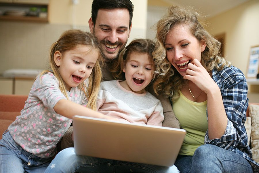 Blog - Excited Family Sitting At Home Using Laptop Together