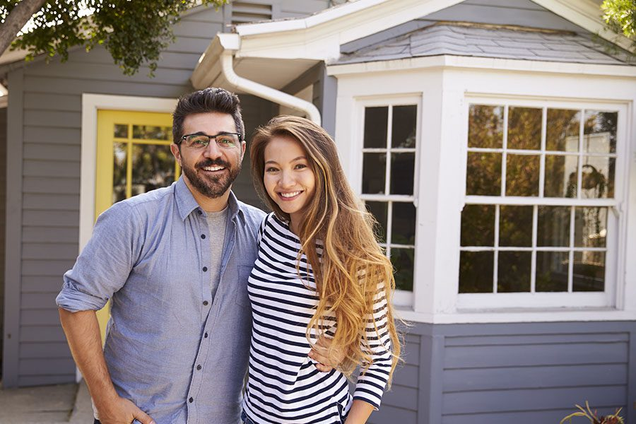 Personal Insurance - Portrait Of Couple Standing Outside Their New Home