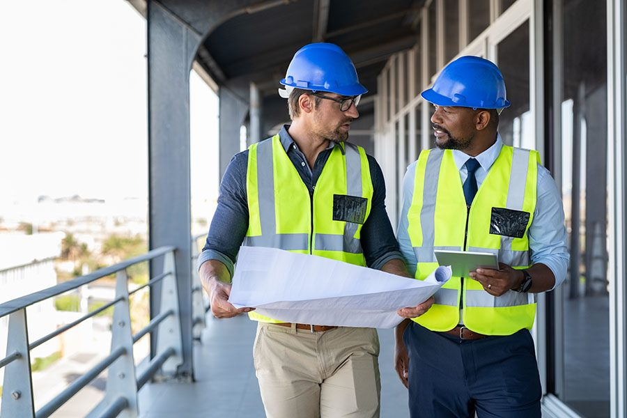 Specialized Business Insurance - Two Architects At Jobsite Looking Over Building Plans