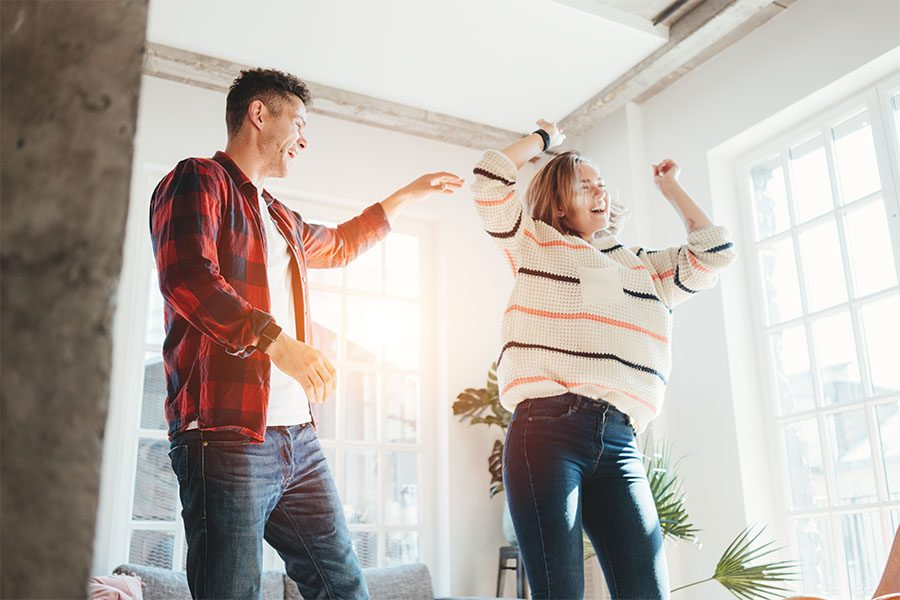 Personal Insurance - Happy Young Couple Having Fun Dancing in the Living Room of Their Spacious New Apartment