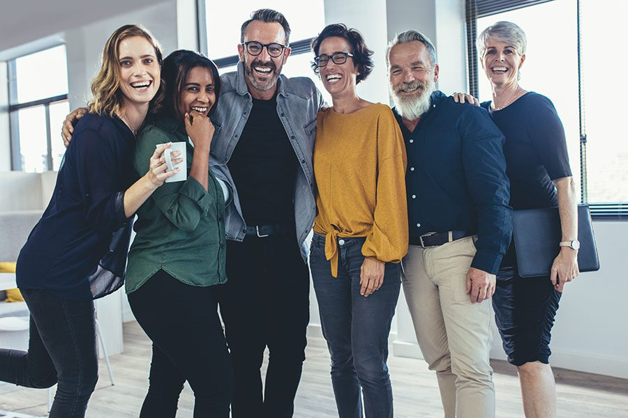 Employee Benefits - Portrait of a Group of Diverse Cheerful Employees Standing in the Office
