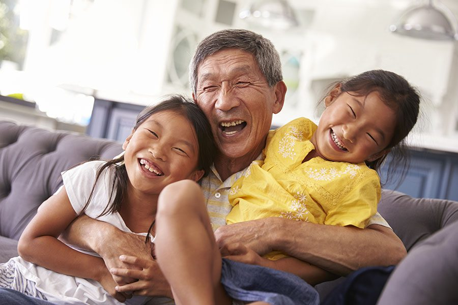 Individual Life Insurance - Portrait of Cheerful Grandfather Playing with His Two Granddaughters in the Living Room