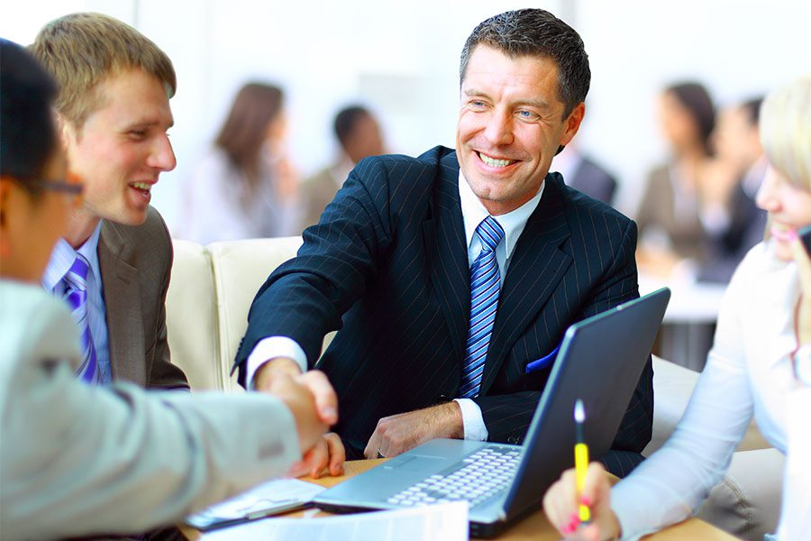 Business Insurance - Businessman Shaking Hands with Clients During Meeting