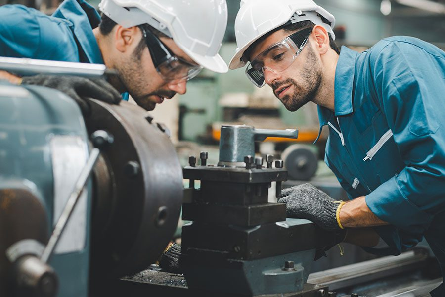 Specialized Business Insurance - View of Two Employees Working on Heavy Machinery in the Factory