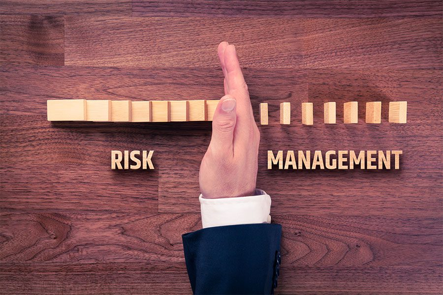 Risk Management - View of Businessman Holding Up His Hand to Stop Blocks From Falling Over in Risk Management Concept