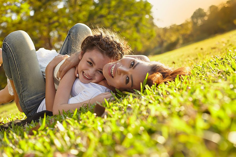 About Our Agency - Closeup Portrait of a Cheerful Mother and Daughter Laying in the Green Grass and Having Fun Playing Together On a Warm Summer Day
