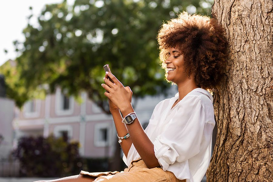 Contact - Closeup Portrait of a Cheerful Young Woman Sitting Next to a Tree in a Quiet Residential Neighborhood in the City While Using a Phone