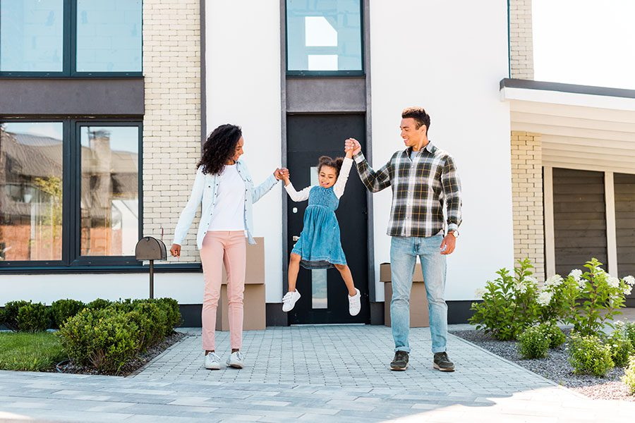 Home and Auto Insurance - Portrait of Happy Parents Holding Up Their Daughter in the Air While Standing Outside Their New Home on a Sunny Day