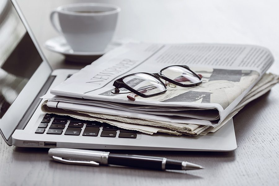 Agency News - Desk with Coffee and Laptop with Newspaper and Glasses Sitting on Top