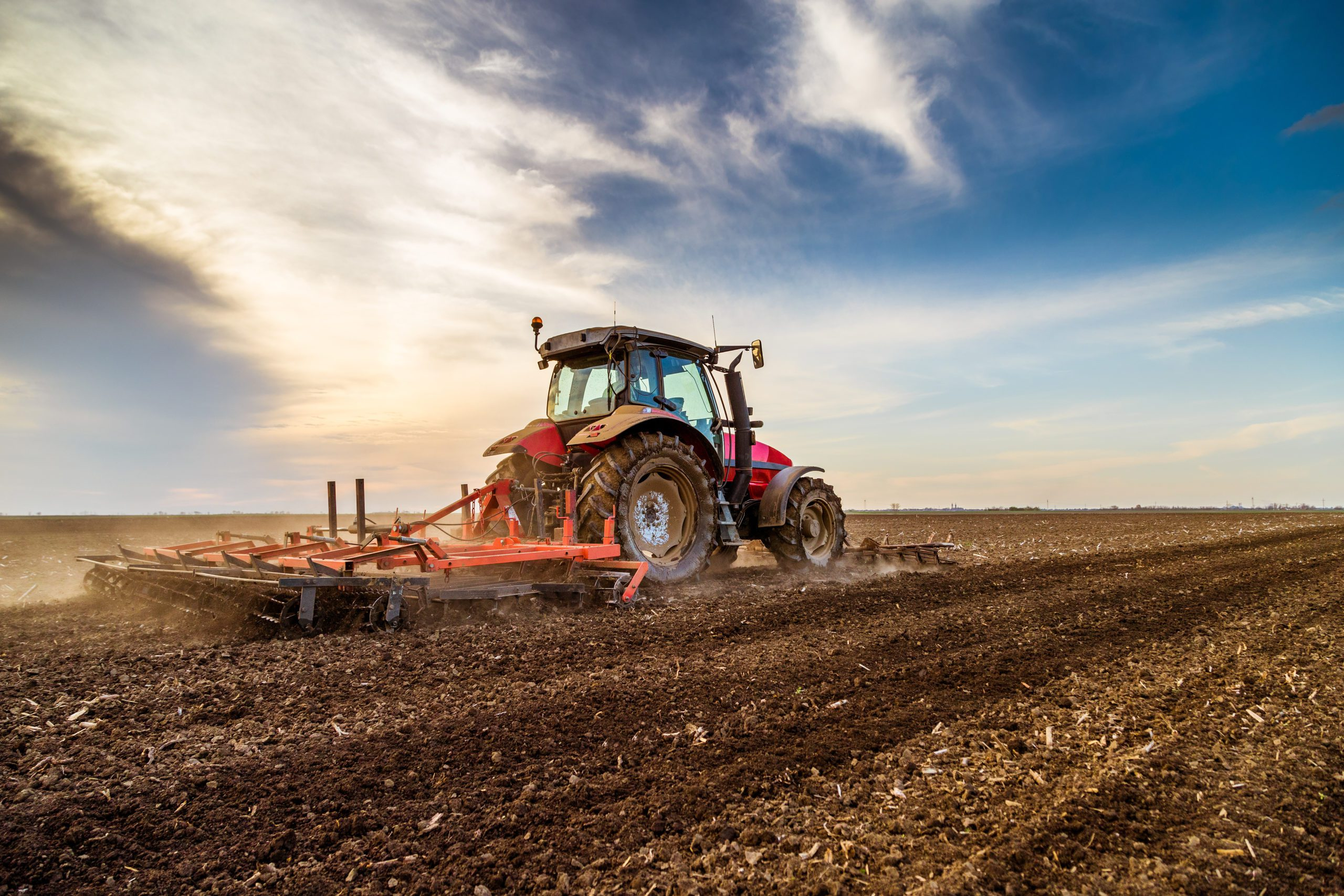 Blog - Tractor cultivating field at spring