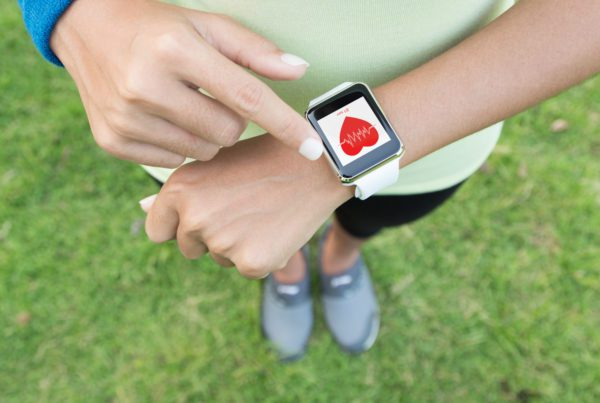 woman checking smart watch for heart rate