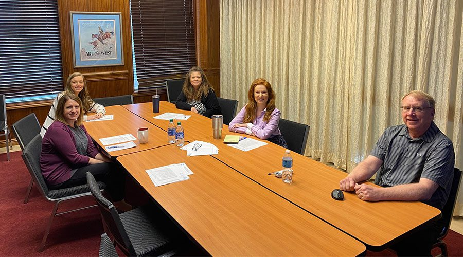 Blog - Men and Women Sitting in Conference Room Discussing Commercial Kitchens in Cincinnati at a Table