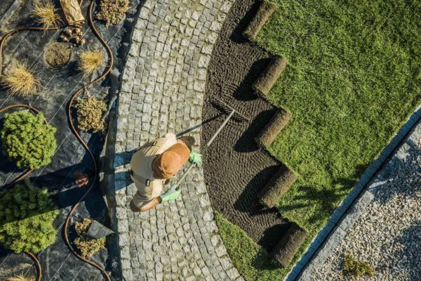 Landscaping-Services-Insurance-Header-Hardworking-Man-Laying-Down-Grass-Next-to-Garden-Beds-in-the-Late-Afternoon