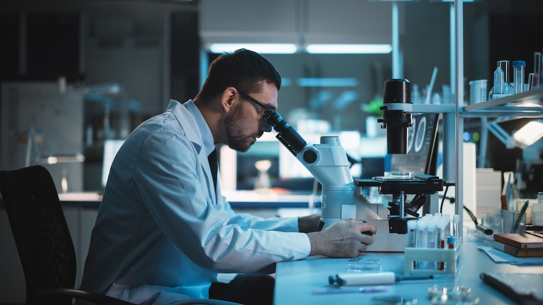 Medical Development Laboratory: Caucasian Female Scientist Looking Under Microscope, Analyzes Petri Dish Sample. Specialists Working on Medicine, Biotechnology Research in Advanced Laboratory