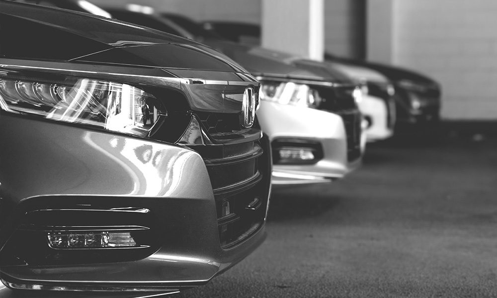 Blog - Grayscale Image of a Line of Shiny Cars in an Indoor Parking Garage