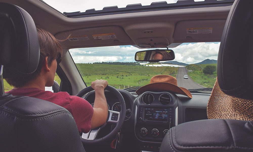 Blog - 8 Ways to Save On Auto Insurance - Looking At A Man From The Backseat View Of Him Driving His Car