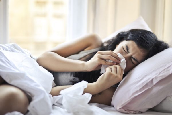 girl sick in bed blowing her nose