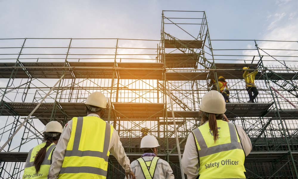 Construction Risk Advisor - Protect Your Employees With Ladder Alternative Programs - Group of Construction Workers Looking up to Scaffolding With a Sunrise Backdrop