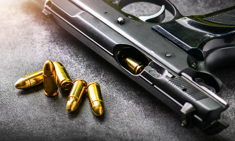 Blog - What Happens When Your Home Insurance Doesn't Cover Self-Defense Shootings - Gun Laying On A Table With Bullets Next to It
