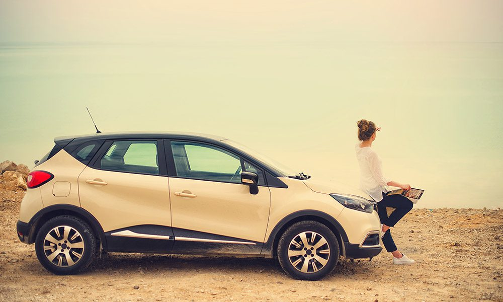 Blog - 8 Insurance Myths - Girl Sitting On Her Car Looking At The Horizon