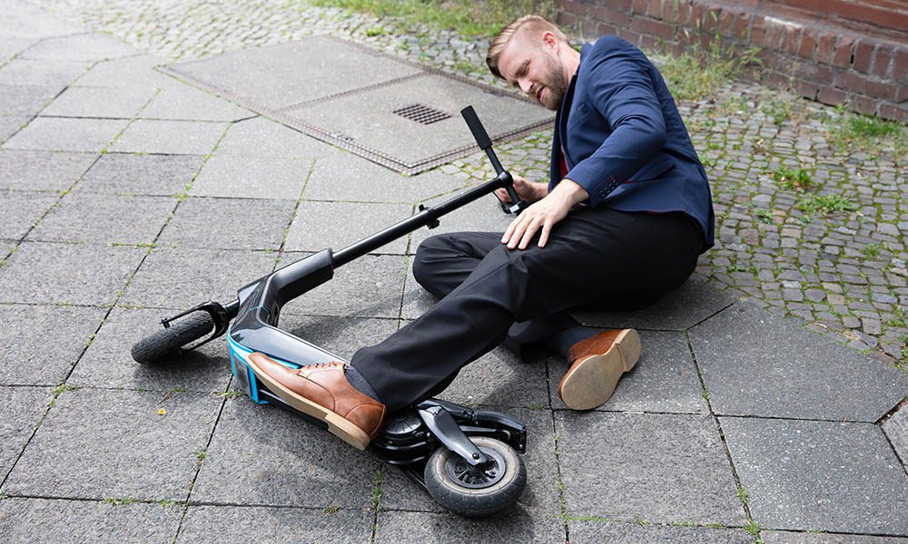 Blog - Shared Electric Scooters - What You NEED to Know - Business Man Crashed On A Scooter
