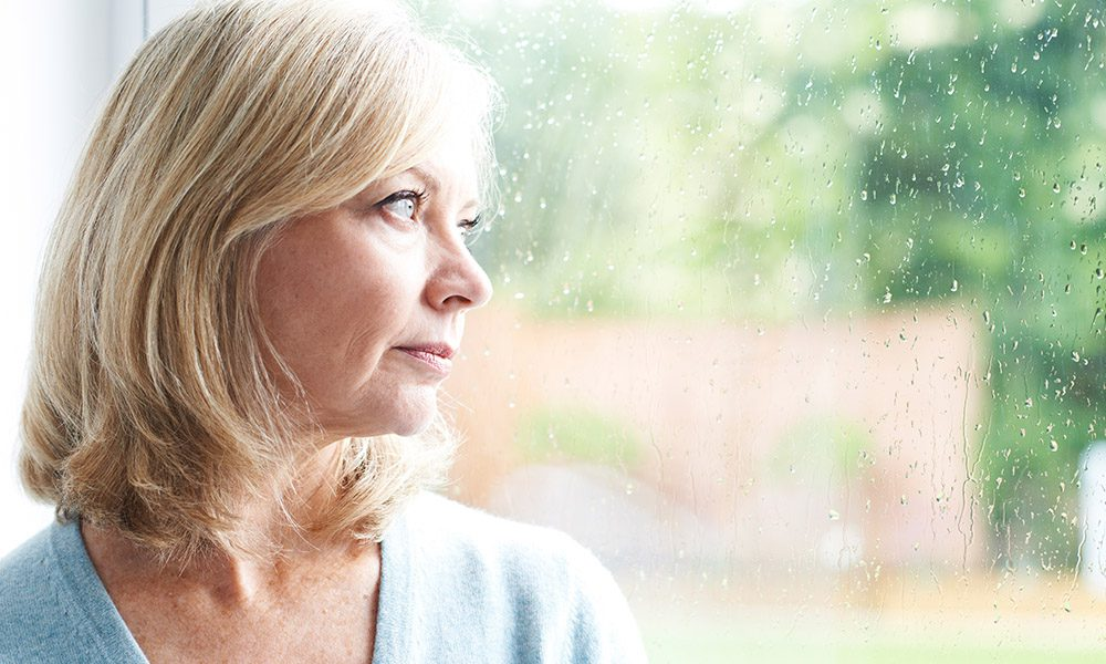 Blog - 4 Tips for Applying for Life Insurance After a Breast Cancer Diagnosis - Woman Looking Out A Window With Rain On It
