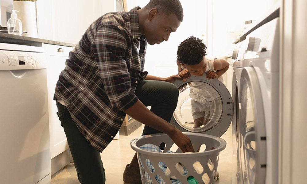 Blog-Dryer Vent vs. Lint Trap-Father-and-Son-Washing-Clothes-in-Washing-Machine-and-Dryer