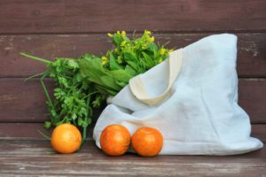 a cotton tote bag with vegetables spilling out of it