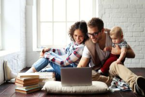 a young family with a child looking at laptop