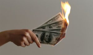 Auto Insurance Gift Card Promotion - Hand Holding One Hundred Dollar Bills On Fire