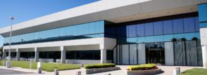 Header - Business Insurance Glass Building with Bright Blue Sky