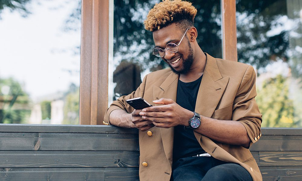Blog - How to Make an Insurance Claim - Young Businessman Working On His Phone Outside And Smiling