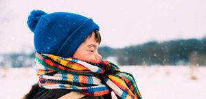 young boy wears scarf and hat on snowy day