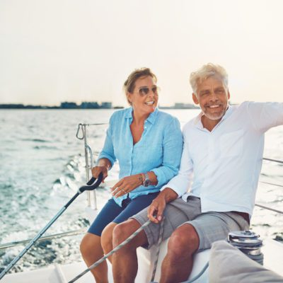 Mature couple sitting together on the deck of their boat enjoying the day sailing on the ocean