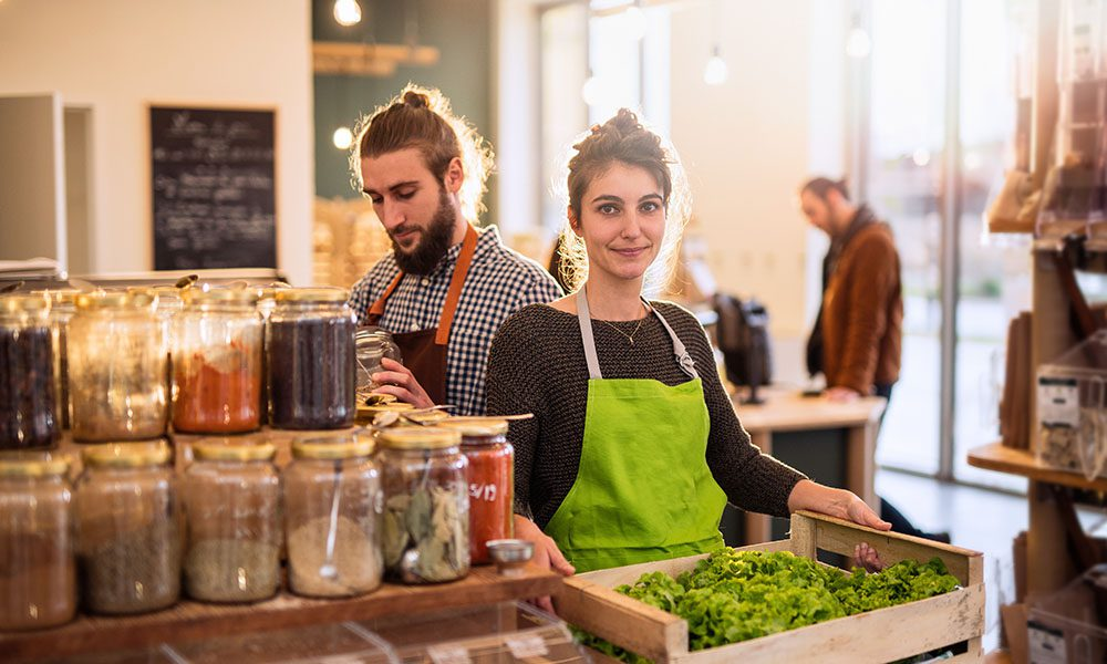 Small Business Resources - Man and Smiling Woman with Aprons Working in Food Market