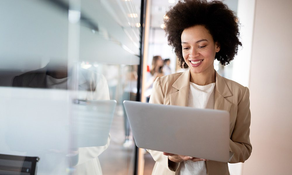 Small Business Resources - Professional Woman Business Owner Smiling at Laptop while Walking Through the Office