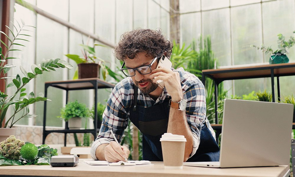 Small Business Resources - Small Business Owner Writing on Documents at Desk While on the Phone and Standing in front of a Laptop