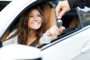 Blog - Woman receiving keys of her new car from dealer