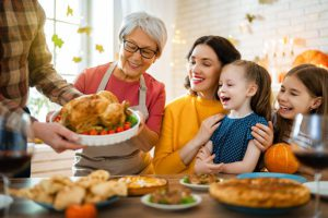 Win a Thanksgiving Turkey For A Friend - Man in A Flannel Giving A Happy Family A Thanksgiving Turkey Meal