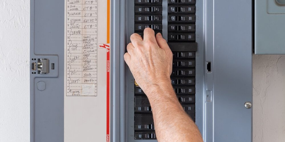 A man inspects an electrical Panel to insure good insurance coverage.