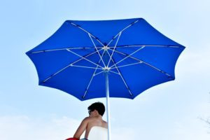 man sitting under a blue umbrella