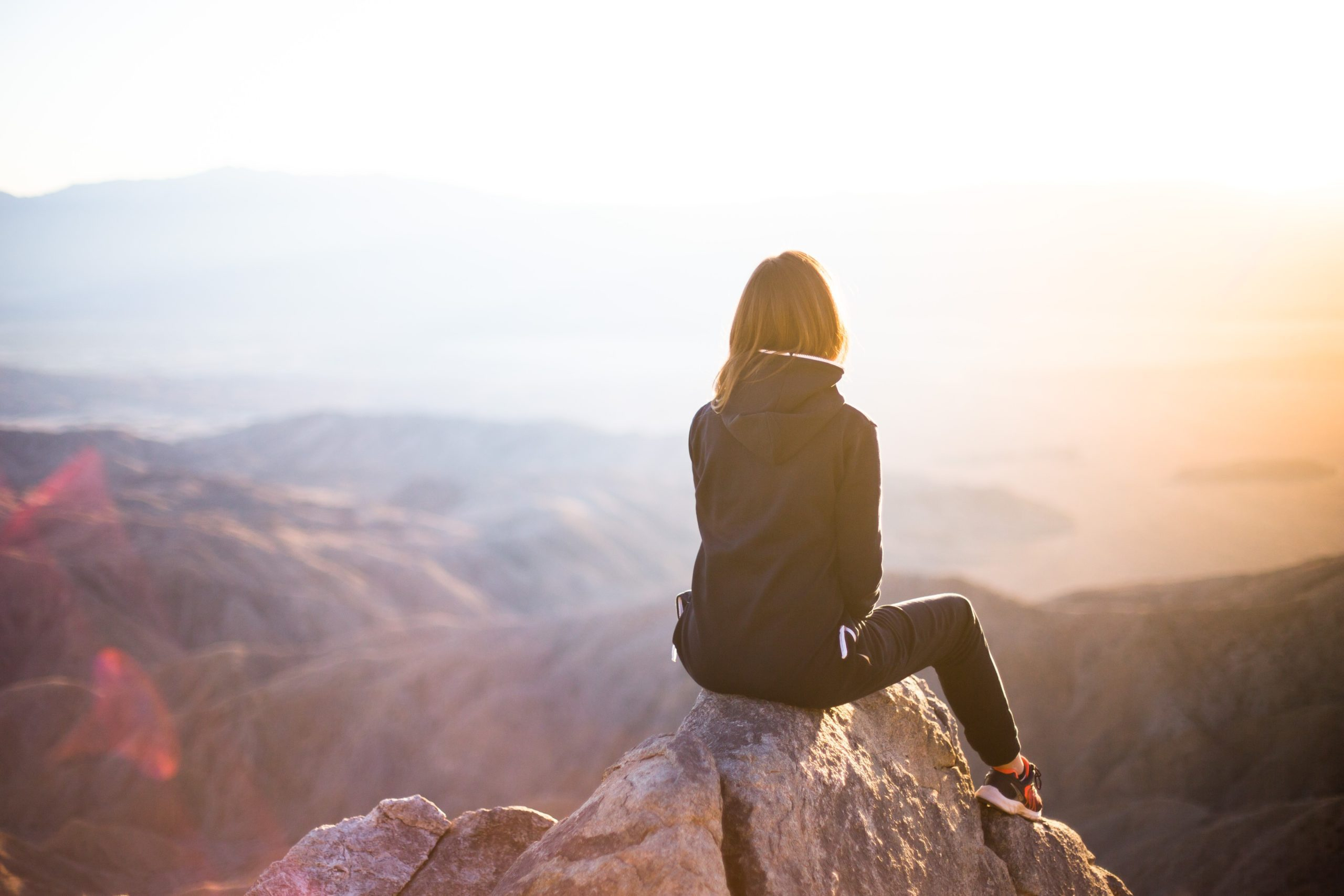 woman in fitness gear sitting on a mountain looking at the sunset