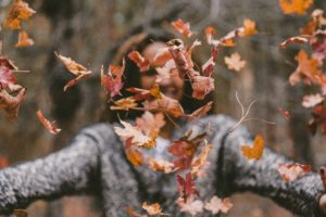 woman throwing fall leaves in the air