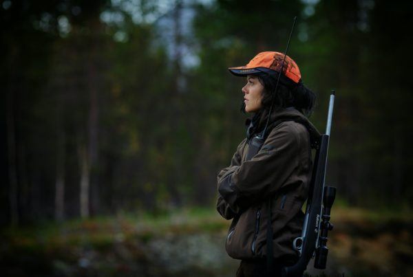 female hunter standing in woods with gun on her back